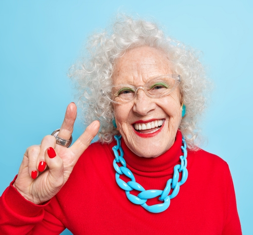 Portrait of cheerful nice looking elderly woman smiles happily m - Portrait of cheerful nice looking elderly woman smiles happily makes peace gesture shows v sign dressed in red jumper with necklace expresses positive emotions isolated over blue background.